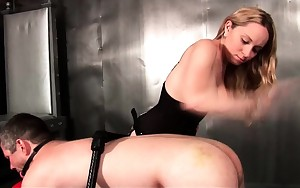 Busty blonde dominatrix slapping male ass
